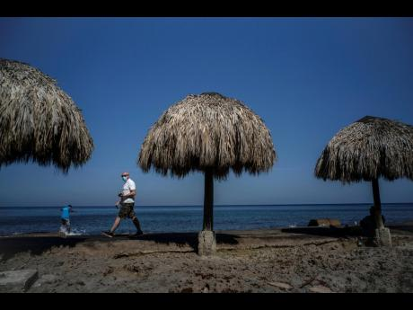 A tourist, wearing a protective face mask amid the new cornavirus pandemic, walks along the beach shore in Havana, Cuba, on Tuesday. The Caribbean is hunting for visitors and vaccines to jump-start the stalled economy in one of the world's most tourism-d