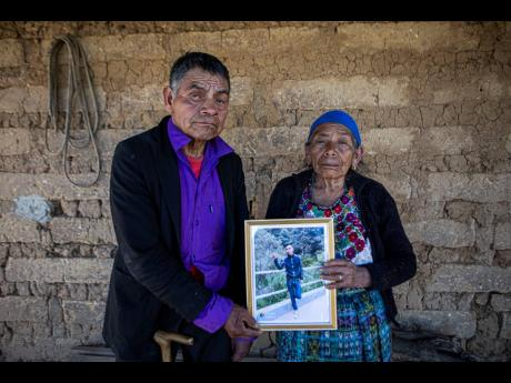 In this January 27 photo, German and Maria Tomas pose for a photo holding a framed portrait of their grandson Ivan Gudiel who they believe is one of the charred corpses found on a rural road on the Mexico-US border township of Camargo, at their home in Com