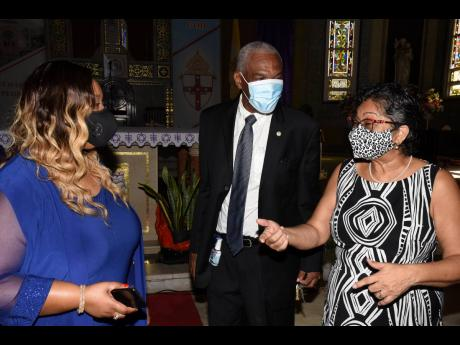 Members of the Jamaica Gasolene Retailers Association engage in last-minute discussions before their 70th anniversary church service at Holy Trinity Cathedral in Kingston on Sunday. From left are Diane Parram, president; Lloyd Chambers, trustee member; and