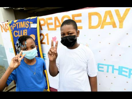 Shamoya James and Tyrese Grant, youth members of the St Matthew's Optimist Club, show the peace sign during a Peace Day initiative at St Matthew's Anglican Church Hall on Weevile Gordon Street in Allman Town, Kingston, on Tuesday.