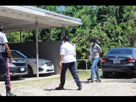 Nadeen Geddes (right) being led by the police from the courthouse in Trelawny. She was sentenced to 20 years for murder and conspiracy to murder for the 2020 killing of her sister, Tamara.