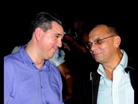 File  In this September 2012 photo, John deSilva (left) and James Rawle converse at a Nestlé Jamaica event in Kingston. Both men now work with the Lasco group.