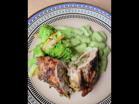 5. The callaloo-stuffed chicken is seasoned with crushed pimento and served with sweet potato gnocchi in a creamy callaloo sauce.