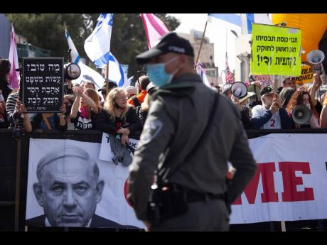 A police officer stands guard in front of protesters as Prime Minister Benjamin Netanyahu's motorcade arrives at the District Court in Jerusalem for a hearing in his corruption trial yesterday.
