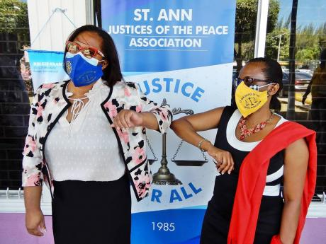 C. Angela Strudwick (left), president of the St Ann Justices of the Peace Association, touches elbow with Marsha Johnson-Henry, JP, at the start of the mask-distribution project in Ocho Rios recently.