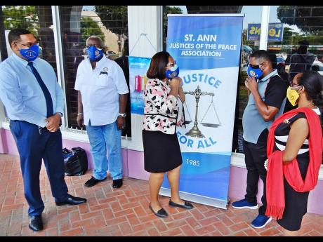 St Ann Justice of the Peace Association president, C. Angela Strudwick (centre), shows Rodney Campbell (second right), how to adjust the mask he was given. Others in the photo (from left) are Paolo Fakhourie, Rotary member; Pixley Irons, JP and president,