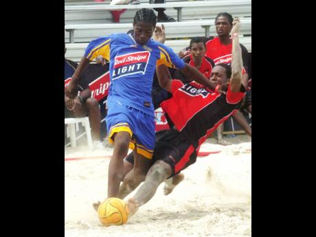 Kenardo Forbes (left), seen here representing Naggo Head, tries to elude Rivoli's Fabian Gordon during the Red Stripe Light Beach Football competition at Hellshire Beach on July 30, 2007. Rivoli won 4-3 in extra time.