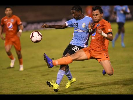 FC Motagua of Honduras' defender Denil Maldonado (right) gets a toe to the ball ahead of Waterhouse's Colorado Murray, in their Concacaf league match at the National Stadium on September 25, 2019. Motagua won 2-0.
